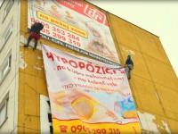 Montáž reklamnej plachty na stenu budovy pomocou horolezeckej techniky
